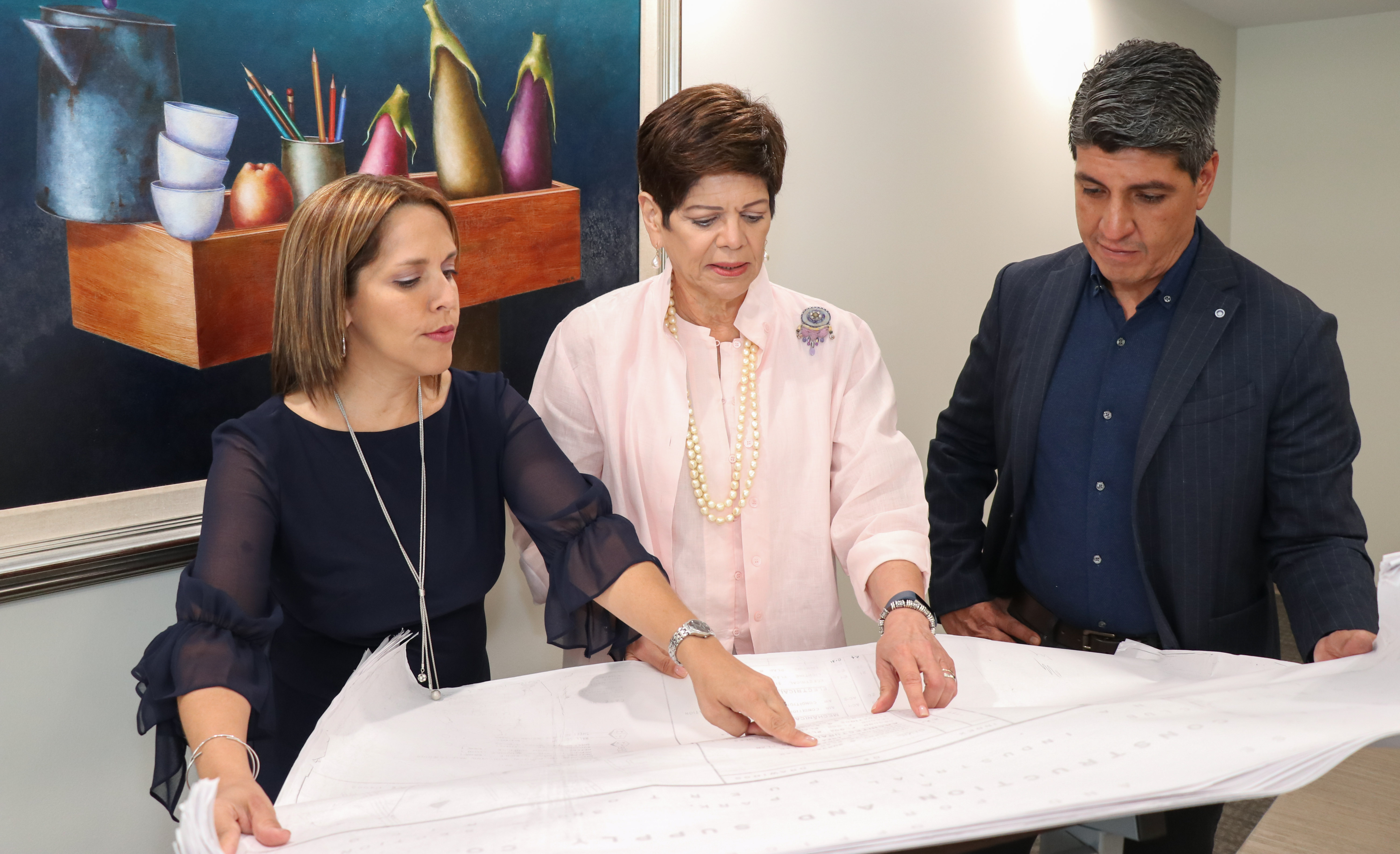 Mariely Rivera, Denisse Santos, e Ivan Baez examine plans for the new food bank.